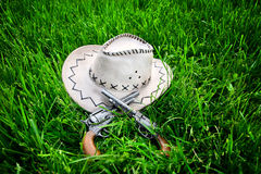Cowboy hat and two guns. Dirty Cowboy hat and two guns on the green grass Stock Images