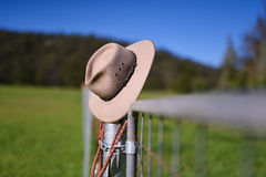 Cowboy hat and whip resting on fence post. Royalty Free Stock Images