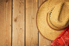 Cowboy hat on wooden vintage table with red bandanna for party invitation. View from above Stock Image