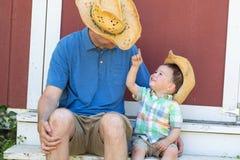 Cowboy Hats för kinesisk son för skämtsam Caucasian fader och för blandat lopp bärande Arkivbilder