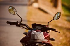 A cowboy hats is kept on a motorbike unique stock photograph. A cowboy hats is kept on the back side of a motorbike  unique stock photograph Royalty Free Stock Photos