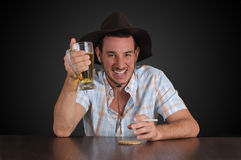 Cowboy having a beer. A happy cowboy having a beer at the local pub Royalty Free Stock Image