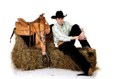 Cowboy on hay. Handsome young cowboy with traditional outfit next to saddle sitting on hay.  Studio shot, white background Royalty Free Stock Photography