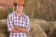 Cowboy hay bales. Handsome cowboy standing against hay bales Stock Photo