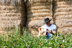 Cowboy by haystack plays guitar horizontal Stock Images