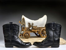 Cowboy High Times. Kids cowboy black boots and chuck wagon with room for your type stock photography