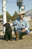 Cowboy with his dog. Kneel down at the Sands Motel at the intersection of Route 54 & 380 in Carrizozo, New Mexico stock photography