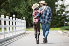 Cowboy with his girlfriend walking on pathway in park at daytime. Back view of cowboy with his girlfriend walking on pathway in park at daytime Stock Photos