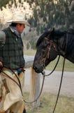 Cowboy and His Horse. Cowboy enjoys a quiet moment with his horse Stock Photos