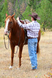 Cowboy. With his horse in the field stock photos