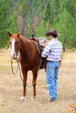 Cowboy. With his horse in the field stock image
