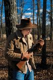 A Cowboy and His Rifle. A cowboy rests against a tree with his trusty rifle at the ready Stock Image