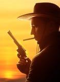 Cowboy in hoed met sigaar en revolver Royalty-vrije Stock Foto's