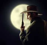 Cowboy holding hat and revolver. Silhouette of cowboy holding hat and revolver outdoor. Full moon Royalty Free Stock Image