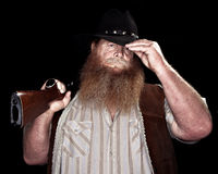 Cowboy holding his rifle while tipping his hat Royalty Free Stock Image