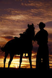 Cowboy holding horse in sunset. A cowboy is standing by his horse in the sunset Royalty Free Stock Photography