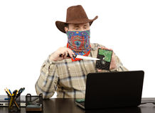 Cowboy holding a knife and hard disk threats on Skype Stock Image