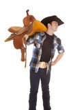 Cowboy holding saddle on shoulder look side Stock Photography