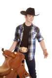 Cowboy holding a saddle smile hand out Stock Photo
