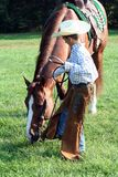 Cowboy with horse. A little boy dressed up as a cowboy, taking his horse for grazing in the fresh green grass stock photography