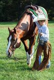 Cowboy and Horse. A little boy dressed up as a cowboy, taking his horse for grazing in the fresh green grass royalty free stock image