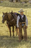 Cowboy with Horse. Cowboy standing by his horse. He has his gun belt, rope, saddle and all he needs to ride the range Stock Photo