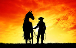Cowboy with horse at sunset Royalty Free Stock Images
