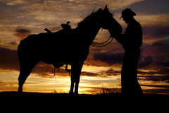 Cowboy horse sunset stand. A cowboy is standing by his horse in the sunset holding its head Royalty Free Stock Photo