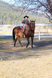 Cowboy and horse. Young cowboy riding his horse on the farm Stock Image
