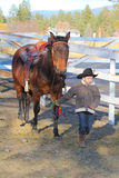 Cowboy and horse. Young cowboy walking his horse on the farm Stock Image
