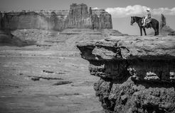 Cowboy on horseback in Monument Valley. Iconic cowboy on horseback on cliff edge at Monument Valley, Utah in black and white stock photos