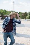 Cowboy i hatten och den rutiga skjortan som ser bort och benägenhet på staketet på ranchen Royaltyfria Bilder