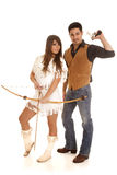 Cowboy and Indian woman gun back bow. A cowboy is holding back his gun while an Indian holds her bow and arrow Stock Images