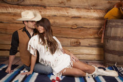 Cowboy and Indian woman her look in front. A cowboy and Indian are sitting on a blanket together Stock Photo