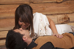 Cowboy and Indian woman laying almost kissing Royalty Free Stock Images