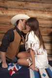 Cowboy and Indian woman sit him kiss cheek Stock Photos