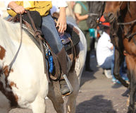 Cowboy with jeans in the stirrup of the horse during the ride Stock Photo