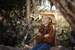 Cowboy kid. A boy with cowboy outfit sitting on a tree trunk, high-key image Stock Photography