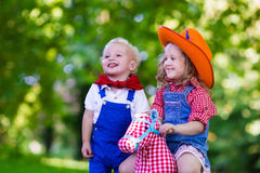 Cowboy kids playing with toy horse. Little boy and girl dressed up as cowboy and cowgirl playing with toy rocking horse in park. Kids play outdoors. Children in Stock Images