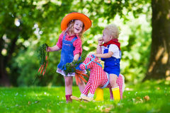 Cowboy kids playing with toy horse. Little boy and girl dressed up as cowboy and cowgirl playing with toy rocking horse in park. Kids play outdoors. Children in Royalty Free Stock Images