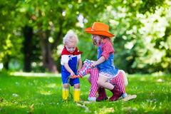 Cowboy kids playing with toy horse. Little boy and girl dressed up as cowboy and cowgirl playing with toy rocking horse in park. Kids play outdoors. Children in Stock Photo