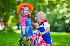 Cowboy kids playing with toy horse. Little boy and girl dressed up as cowboy and cowgirl playing with toy rocking horse in park. Kids play outdoors. Children in Royalty Free Stock Photography