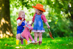 Cowboy kids playing with toy horse. Little boy and girl dressed up as cowboy and cowgirl playing with toy rocking horse in park. Kids play outdoors. Children in Stock Photography
