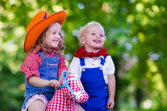 Cowboy kids playing with toy horse. Little boy and girl dressed up as cowboy and cowgirl playing with toy rocking horse in park. Kids play outdoors. Children in stock image