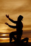 Cowboy kneel silhouette both hands up. A silhouette of a cowboy on his knee with arms up royalty free stock image