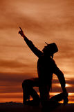 Cowboy kneel silhouette point up. A silhouette of a cowboy reaching his arm up to the sky royalty free stock photos