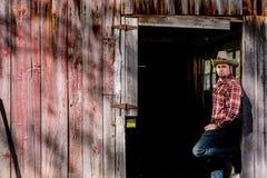 Cowboy Leaning in Barn Door stock images