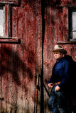 Cowboy Leaning on Barn Looking into the Sun Stock Photos