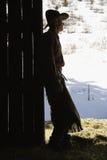 Cowboy Leaning in Doorway of Barn. Silhouette of a cowboy leaning in a barn doorway, looking outside. Vertical shot Stock Image