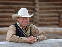 Cowboy Leaning on Fence. Cowboy leans on fence with log building behind him Stock Photos